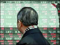 Japanese businessman gazes at a share prices board in Tokyo