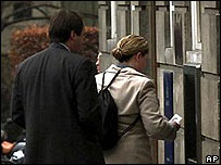 Bank customers queue at a cash machine