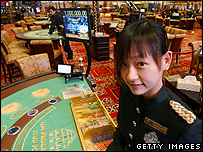 A young worker waits by a poker table at a casino in Macau