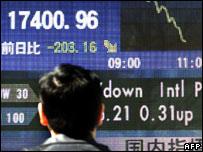 Hombre ante un tablero de transacciones en Japón