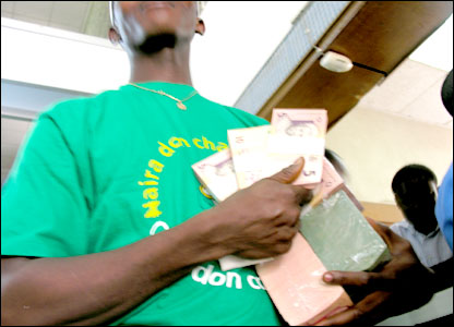 A bank official holds up the new naira notes