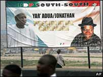 People pass a billboard of presidential candidate Umaru Yar'Adua and his running mate Goodluck Jonathan in Port Harcourt. File photo