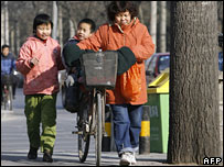 An adult and two children on a Beijing street