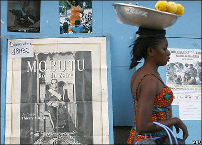 A street vendor passes in front of movie posters in Ouagadougou