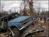 A battered truck rests against a broken tree after a tornado in Caulfield, Missouri
