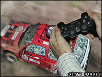 PS3 controller in front of a screen showing a driving game