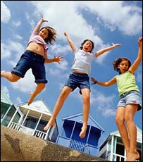 Kids jumping up in front of beach huts
