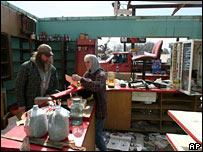 A man and a woman sift through papers at a damaged garage in Missouri