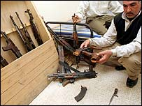 A man holds a damaged rifle at the National Iraqi Intelligence Agency headquarters