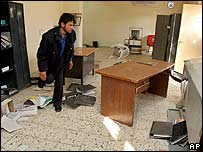A man stands amid scattered furniture and office material at the National Iraqi Intelligence Agency headquarters
