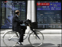 A man cycles past a screen showing Japan share prices