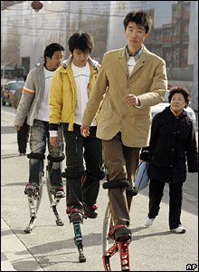 A woman watches three young men stride past on strap-on leg springs in the Chinese capital, Beijing