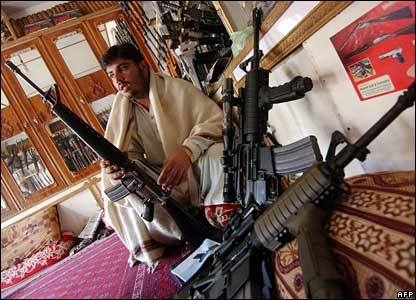 A Pakistani shopkeeper displays an M-16 and other guns in his shop in an area near the Afghan border