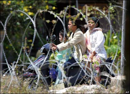 A family rides past a razor wire fence on a motorbike in Pattani, Thailand