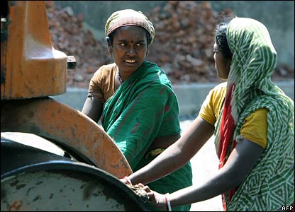 Indian women labourers push a steamroller at a construction site in Kolkata