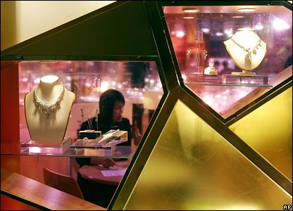 An exhibitor sits behind coloured glass in a booth at the Hong Kong International Jewellery Show