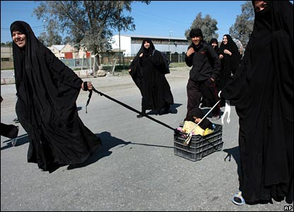 Iraqi women on a pilgrimage to Karbala pull a small child in a plastic box along the road.