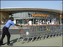 Man pushing trolleys outside Sainsbury's store