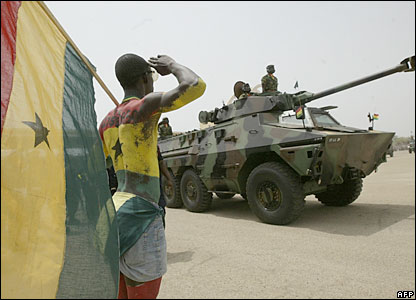 A man painted in Ghana's national colours salutes a tank