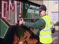 A member of the graffiti removal team taking the road sign down