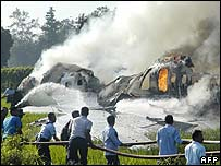 Rescue workers try to put out the flames of a Boeing 737-400 in Indonesia