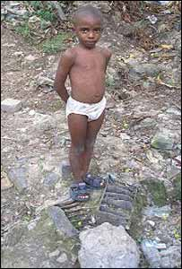 Un niño de Haina, semidesnundo, parado sobre los restos de una batería de automóvil / Foto: Blacksmith Insitute