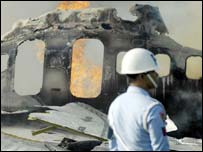 An Indonesian official stands near the wreckage of the plane