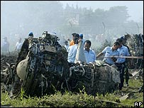 Investigators look at the wreckage of an Indonesian Boeing 737-400