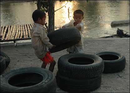 Young Burmese boys helping to stack tyres due to go across the river