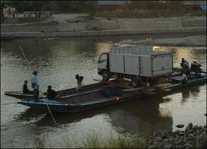 Truck being rowed over the river from Thailand to Burma