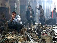 Iraqi men amid bomb debris