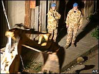 UN soldiers look on as a bulldozer pulls down the wall.