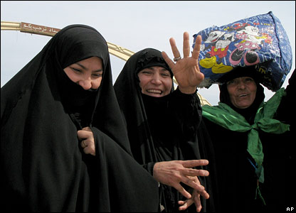 Iraqi women on their way to Karbala smile as they walk down a street in Baghdad on 8 March