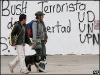 """Dos hombres caminan delante de una pintada en Bogot�, que reza """"Bush terrorista"""""""