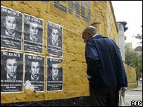 """Un hombre se detiene a leer pegatinas con la foto de Bush, que rezan: """"Se busca por cr�menes de guerra"""""""