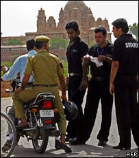 Security guards speak to a policeman on a motorbike