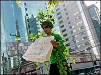 Protester holds banner reading 'Hold a tree' outside Sao Paulo's Hilton Morumbi Hotel