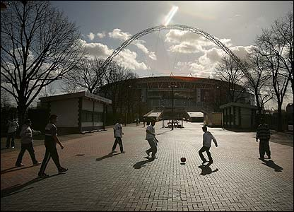 Children play football outside the new Wembley Stadium on the day the FA is given the keys to the stadium