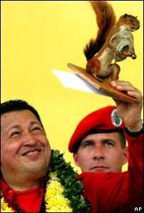 Hugo Chavez holds up a stuffed squirrel given to him as a gift in Trinidad, Bolivia