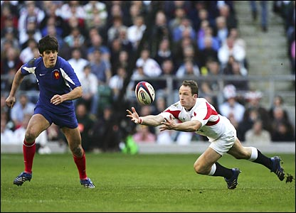 England's Mike Catt juggles the ball as David Skrela looks on