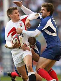 England fly-half Toby Flood (left) tries to hold off France wing Vincent Clerc