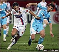 Milan Baros (izq.), del Lyon, pelea la pelota con Lorik Cana, del Marsella.