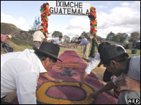 Indigenous men  put the finishing touches on a welcoming carpet in Chimaltenango, west of Guatemala City