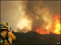 A firefighter hoses down the brush in Orange County, California