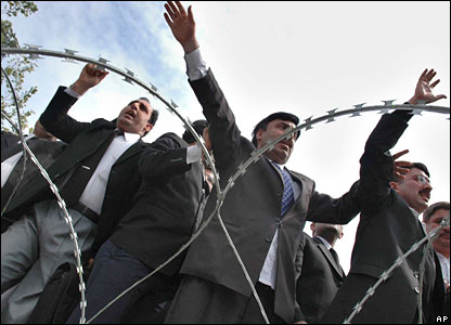 Lawyers chant slogans behind barbed wire in Peshawar