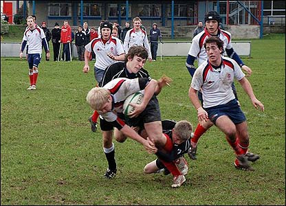 David Tinkler and Stuart Francis of Ards RFC bring down Connor Piper of Malone