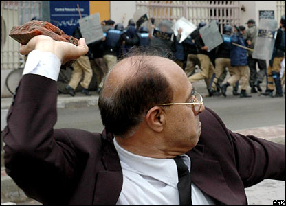 A lawyer is poised to throw a brick during protests in Lahore