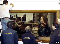 Workers take down Da Vinci's Annunciation at the Uffizi museum in Florence