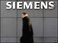 Man walks past a Siemens logo