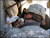 US soldier tends to an Iraqi boy's wound